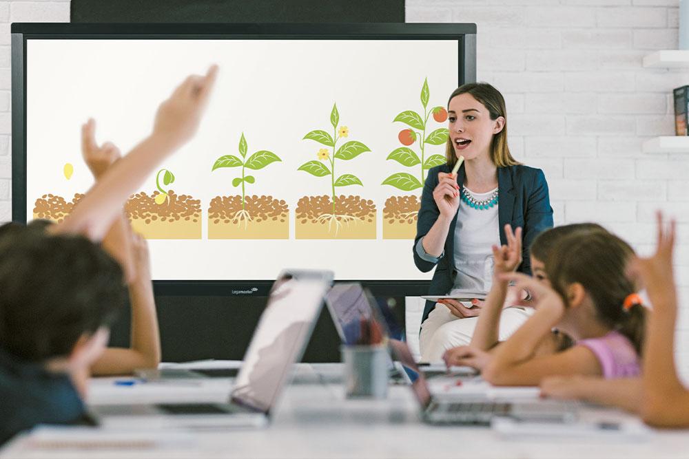 Unterrichtspraxis Lehrerin vor einer digitalen Tafel