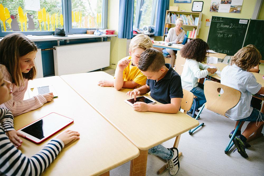 DigitalPakt Schüler in digitale Klasse mit Tablet und Notebook