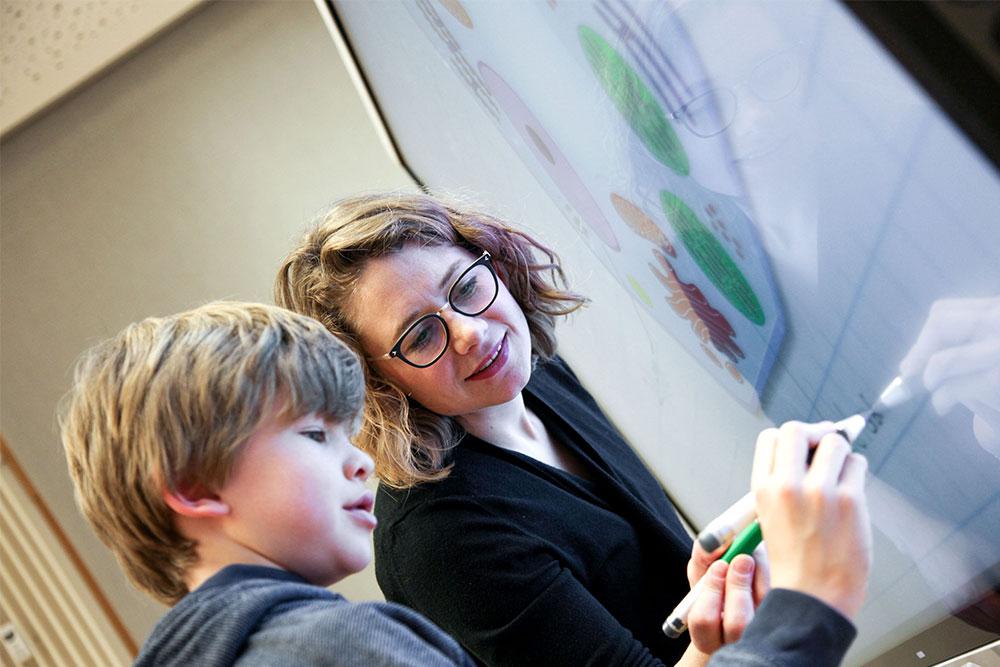 Fortbildungen Lehrerin und Schüler vor digitalen Tafel